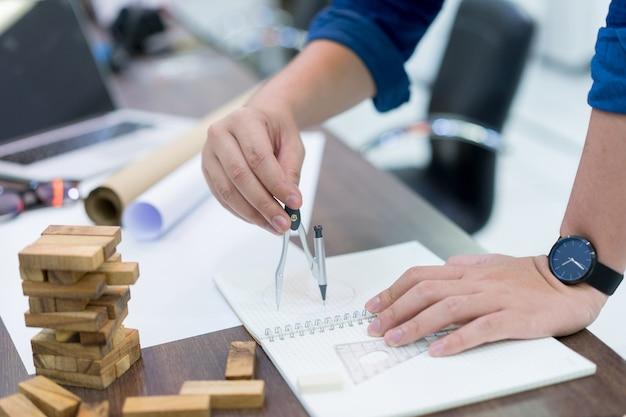 스케치에 건축 작업의 계획 설계를 그리기 위해 나침반을 사용하여 엔지니어링 사람 손