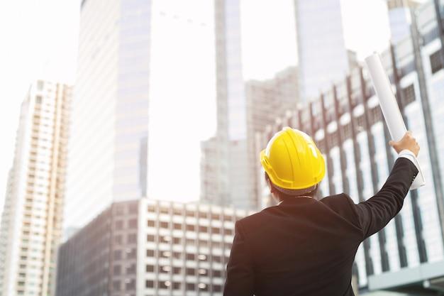 엔지니어링 남자 정장 건설 노동자는 작업 작업의 안전을 위해 안전 헬멧을 착용합니다. 엔지니어 서 청사진 종이 제기 팔 주먹 쾌활 한 쇼 프로젝트 성공.