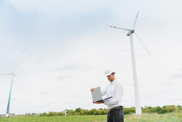 Инженер, использующий ноутбук для проверки ветряного генератора электроэнергии на открытом воздухе, голубое небо и облачный фон