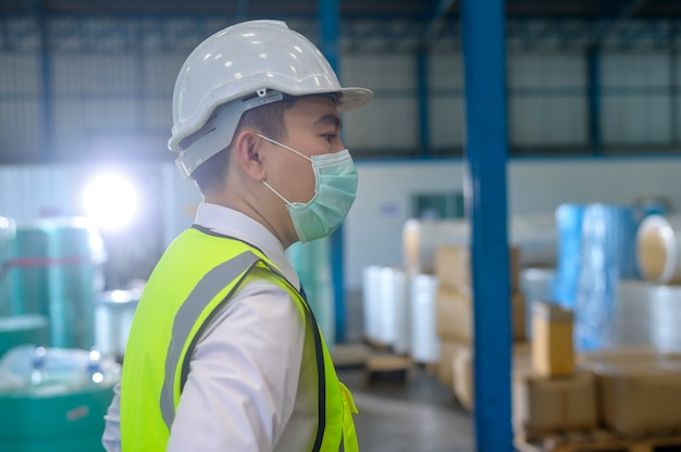 An engineering man wearing medical mask , protective helmet working in warehouse factory