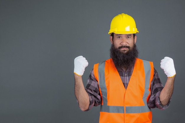 An engineering man wearing a yellow helmet wearing white gloves showed a gesture on a gray .