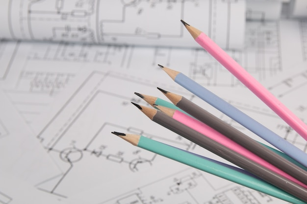 Engineering pencils on background of electrical engineering drawings.