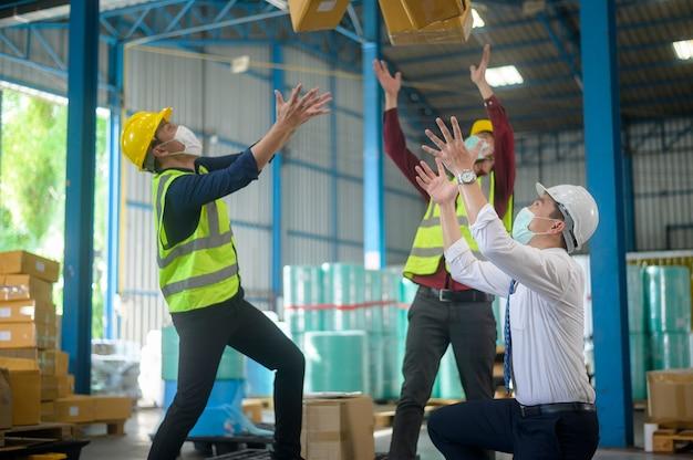 エンジニアリングの人々は、現代の工場で幸せなフェイスマスクを着用しており、産業の成功とチームワークの概念