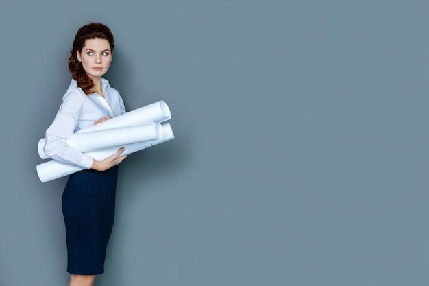 エンジニアリングプロジェクト。エンジニアリングプロジェクトに取り組んでいる間、青写真を立って保持しているスマートで素敵な快適な女性