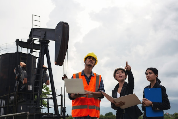 The engineering team stands beside working oil pumps with a sky .
