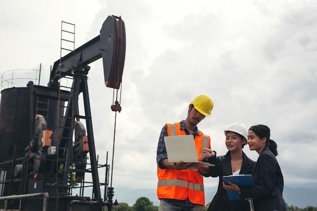 Il team di ingegneri sta accanto alle pompe dell'olio funzionanti con un cielo.