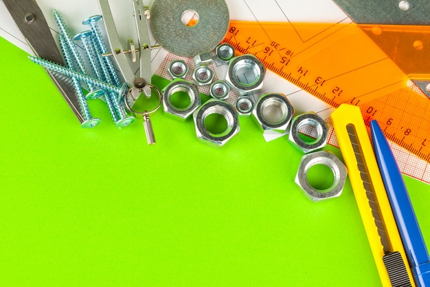 Engineering tools. bolts and nuts on green