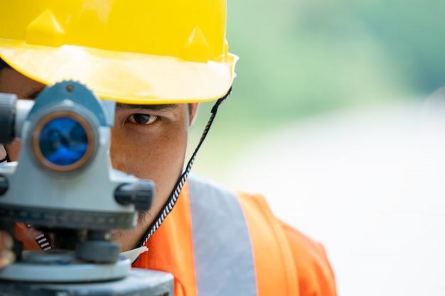 エンジニアリングはセオドライトを使用して、建設中の新しい道路を示します。
