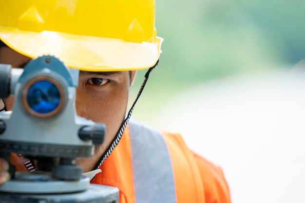 Engineering use theodolite mark a new road under construction.