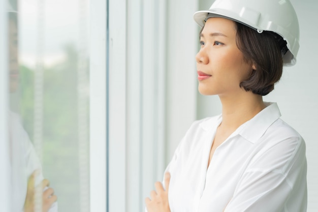 Engineering woman arm cross and looking outside office with vision for successful lifestyle