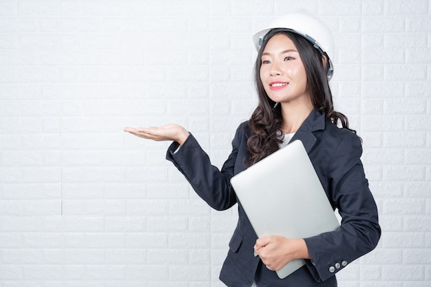 Engineering woman holding a separate notebook, white brick wall made gestures with sign language.