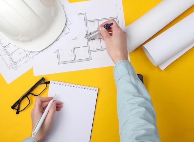 엔지니어링 작업 공간. 여성의 손은 노란색으로 계산하고 측정합니다.