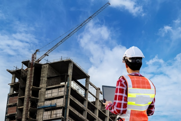 エンジニアは高層ビルの建設計画に取り組んでいます。エンジニアの建物のコンセプト。