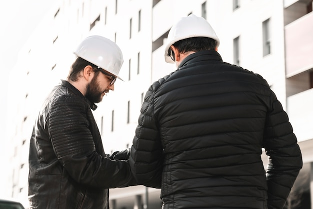 Engineers discussing plans on street
