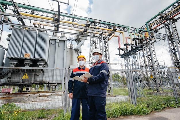 엔지니어 전기 변전소는 범 혈증 발생 당시 마스크에서 현대식 고전압 장비를 조사합니다. 에너지. 산업.