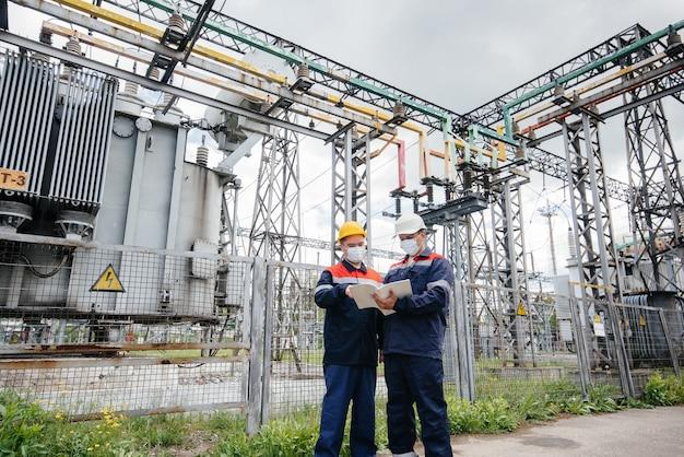 Инженеры электрических подстанций проводят обследование современного высоковольтного оборудования в маске во время пандемии. энергия. промышленность.