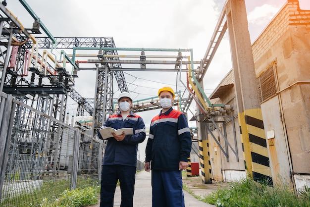 エンジニアの電気変電所は、パンデミア時に夕方にマスク内の最新の高電圧機器の調査を実施します。エネルギー。業界。