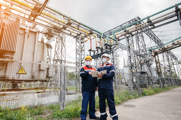 Engineers electrical substations conduct a survey of modern high-voltage equipment in medical masks
