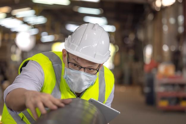 エンジニアは工場で新しいコーティングされたパイプを調べます