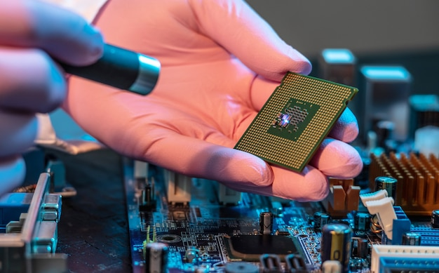 The engineers gloved hand is holding the cpu chip against the background of the motherboard