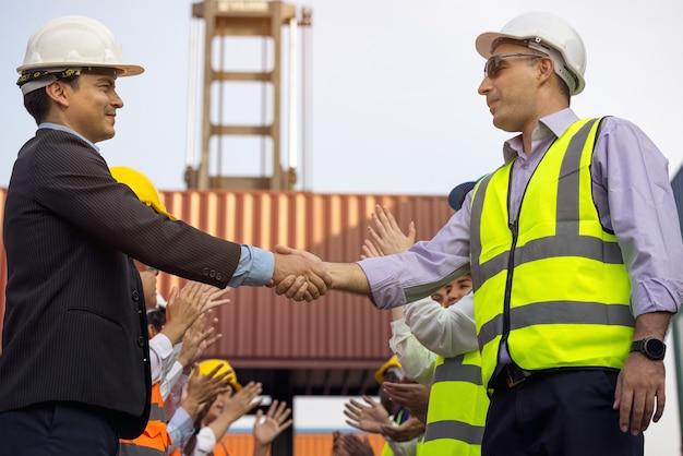 労働者やビジネスでの会議が成功した後、建設現場でハンドシェークを行うエンジニア
