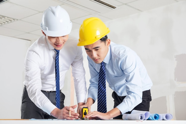 Engineers in helmets standing by the factory