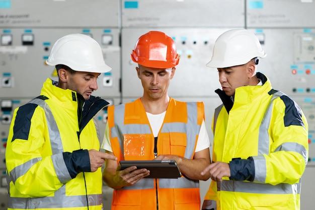 Инженеры в форме и касках с цифровым планшетом проводят пуско-наладочные работы, проверяя электрические параметры.