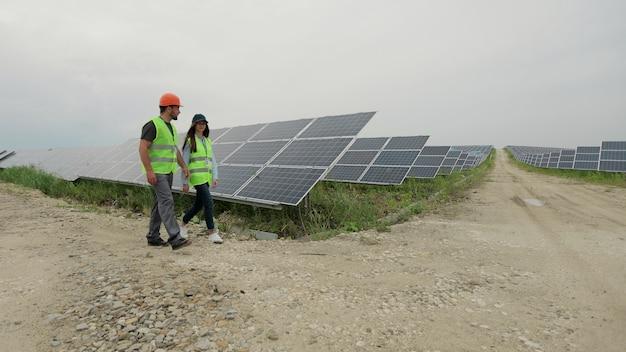特別なユニフォームウォーキングでソーラーパネルを検査するエンジニアの男性と女性が、日当たりの良いバッテリーの設置について話し合います。電気エンジニアの環境。クリーンエネルギー生産。