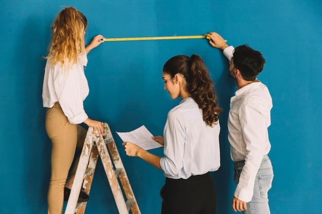 Engineers measuring wall