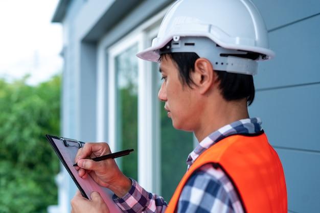 주황색 반사 조끼를 입은 엔지니어 또는 검사관이 건물 건설 현장에서 메모를 하고 클립보드, 계약자 검사 및 엔지니어링 개념을 확인하고 있습니다.