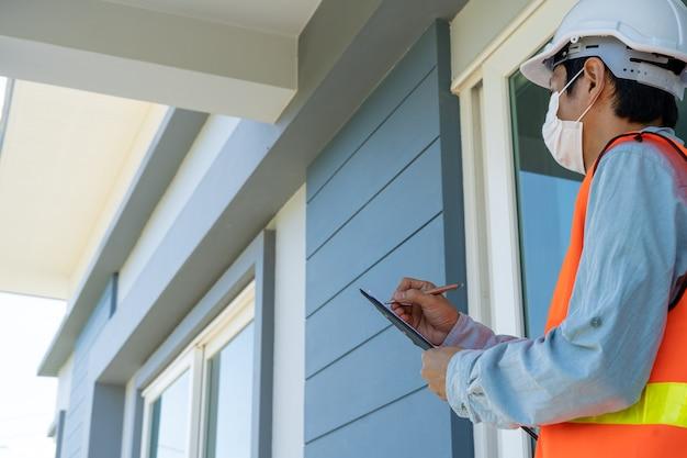 주황색 반사 조끼를 입은 엔지니어 또는 검사관이 건물 건설 현장에서 메모를 작성하고 클립 보드로 확인합니다.