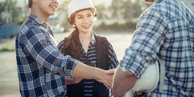 技術者たちは側で秘書の女の子と一緒に手を振る。