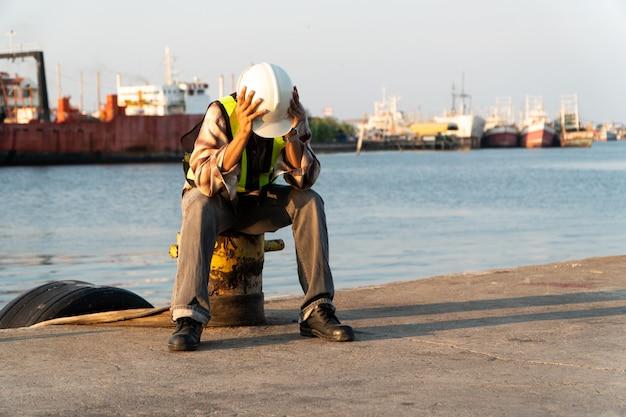 안전 헬멧을 착용하고 앉아 엔지니어들은 실망하고 열심히 후회하며 실패했습니다.