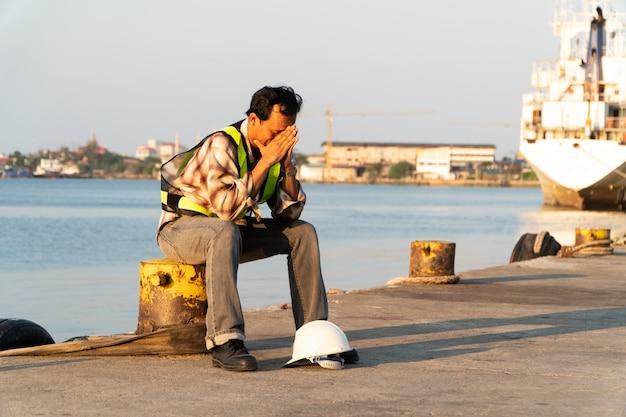 앉아서 안전 헬멧을 착용하는 엔지니어. 그는 피곤하고 실망하고 열심히 일한 것을 후회하고 실패했다고 느꼈습니다.