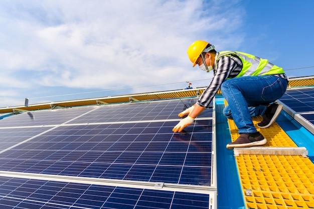 Инженеры используют портативный компьютер для проверки солнечных панелей на электростанции, на которой установлены солнечные панели, использующие солнечную энергию.