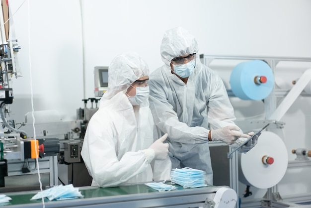 Engineers wear personal protective equipment or ppe checking machine in face mask production factory