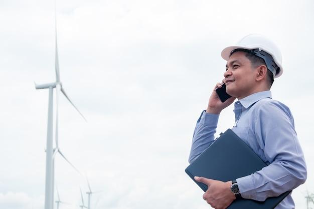 エンジニアの風車は、風力タービンを背後に置いてスマートフォンで作業しています