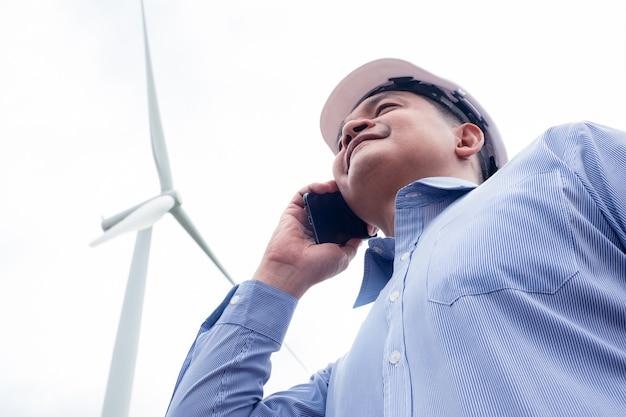 엔지니어 풍차가 풍력 터빈을 뒤로하고 스마트 폰에서 작업하고 있습니다.