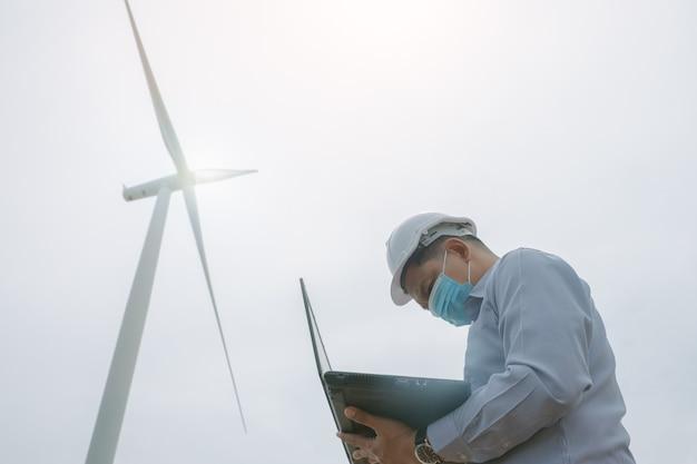 フェイスマスクを着用し、バックグラウンドで風力タービンを使用してラップトップで作業しているエンジニアの風車