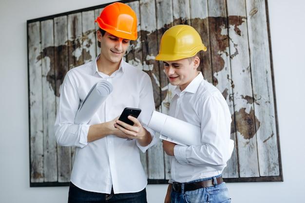 オフィスで作業中のヘルメットを持つエンジニア