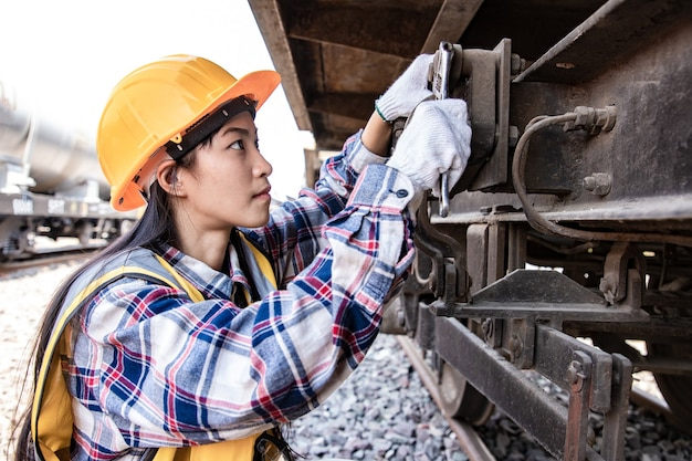 Engineers woman working on train garage site and using wrench for repair traction motor of train