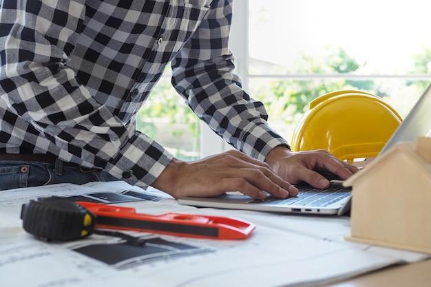 엔지니어는 랩톱 및 청사진으로 작업합니다. 건설 프로젝트 계산 및 확인