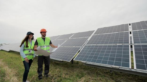 태양열 계획을 손에 들고 태양광 패널 스테이션 근처에 서 있는 엔지니어 노동자