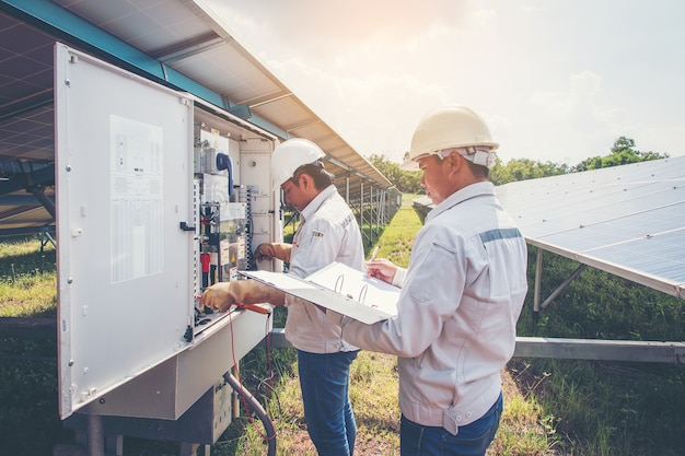 Engineers working on monitoring and maintenance equipment: cheking inverter status