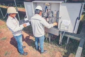 Engineers working on monitoring and maintenance equipment: cheking inverter status