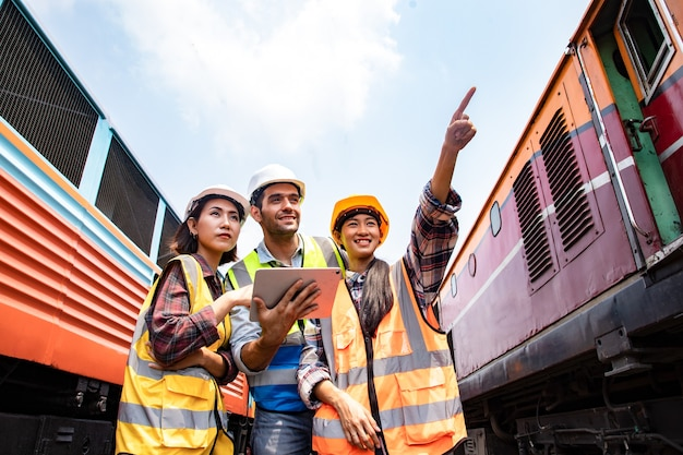 Инженеры, работающие над статусом железнодорожного поезда и держащие ноутбук для планирования и встреч
