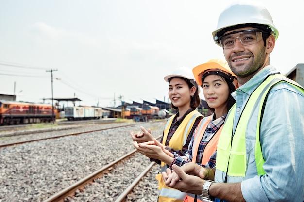 電車のガレージ サイトで作業するエンジニアは眼鏡をかけ、成功のために手をたたく