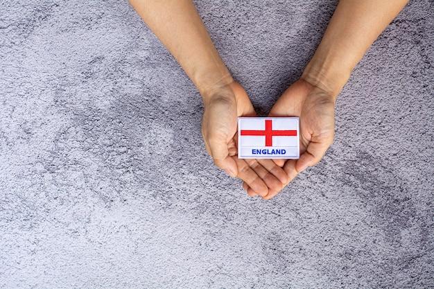 Флаг англии в его руке. - любовь, забота, защита и безопасная концепция.