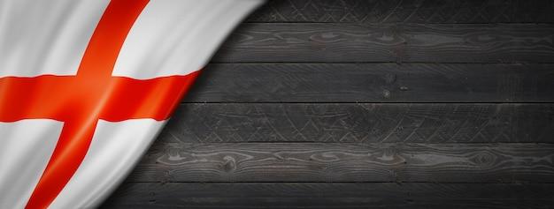 Флаг англии на черной деревянной стене. горизонтальный панорамный баннер.