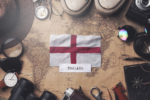 England flag between traveler's accessories on old vintage map. overhead shot